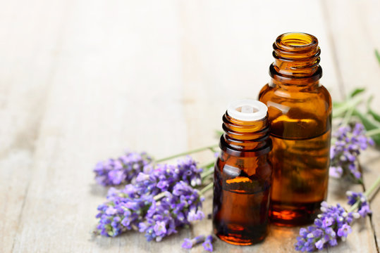 Lavender essential oil in the amber bottle, on the wooden table