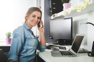 Woman working at home office while talking on phone