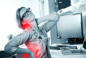 Woman in home office suffering from backache sitting at computer desk