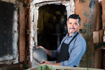 gay male with black-glazed ceramic vase standing close to kiln