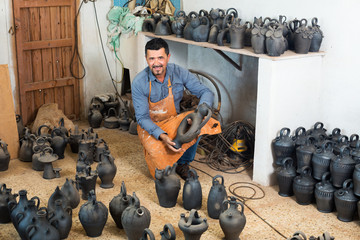 Potter sitting with ceramics vessels