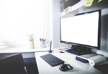 Desktop computer on desk in home office interior, blank screen