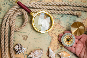 Old vintage retro compass,  magnifying glass on ancient world map.