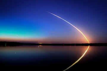 Space Shuttle Launch into a blue sky at dawn with reflection on the water