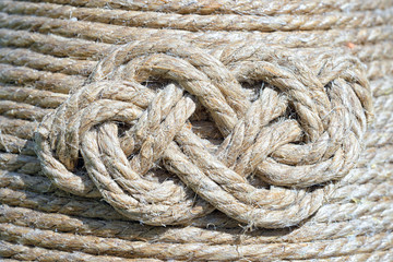 endless eternal macrame knot on the background of the hemp rope