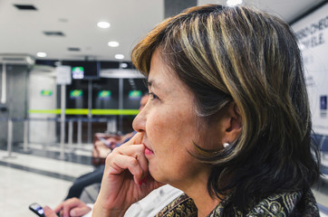Close up on a woman waiting anxious on the airport's departure lounge