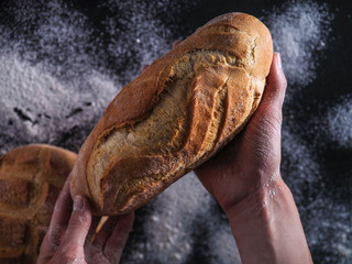 Baker's hands hold fresh bread
