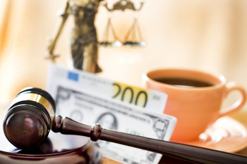 Law concept. Gavel, statue, money and coffee on wooden table