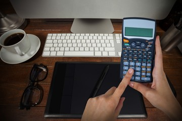 Composite image of hands of businesswoman using calculator