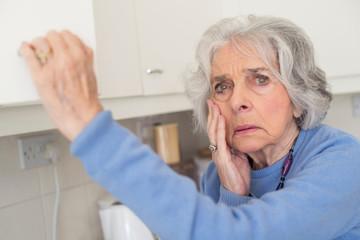 Forgetful Senior Woman With Dementia Looking In Cupboard