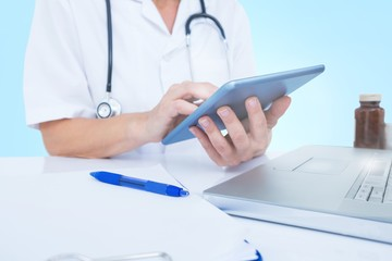 Midsection of female doctor using digital tablet