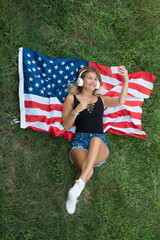 American blonde woman resting on grass with american flag doing a selfie with her phone