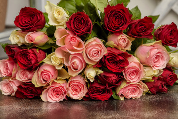 Big bouquet of multicolored roses, on table