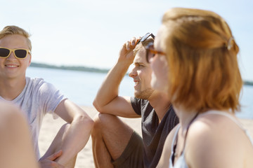 man sitting on a beach with friends on a hot sunny day