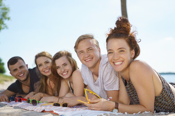 Happy trendy young students lying on a beach