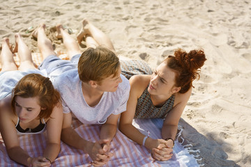 Young couple lying chatting on a beach
