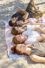 Young friends dozing on a sandy beach