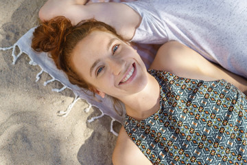 Happy relaxed young woman lying on a beach