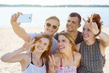 Happy group of young friends taking a selfie on the beach
