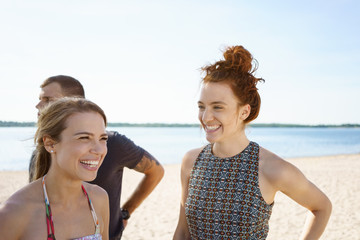 Laughing young women on the beach sharing a joke with her friends