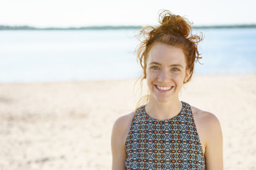 young woman with a lovely warm smile on the beach