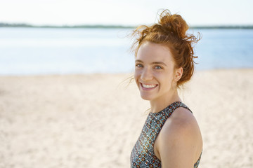 Attractive young redhead woman standing on a beach