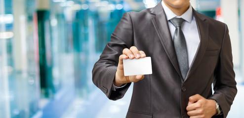 Businessman shows a payment card .