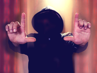Hacker without face holding hands in the air on distorted colorfull background. Hacking concept illustration