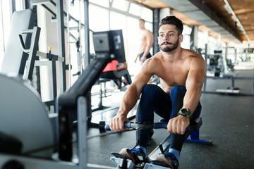 Young handsome man workout with rowing machine