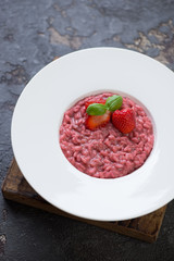 Strawberry risotto served in a white plate over brown stone background, vertical shot