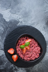 Stone slate tray with a bowl of strawberry risotto, above view over grey stone background with space, vertical shot