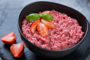 Risotto with strawberries served in a black bowl, selective focus, close-up