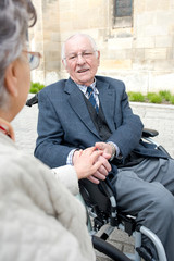 woman holding hand of senior man in wheelchair talking