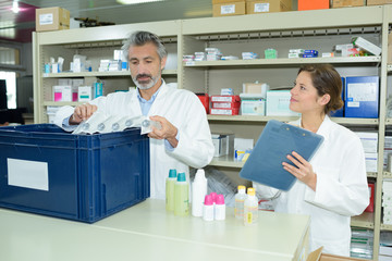 male and female pharmacists maintaining checklist at counter in pharmacy