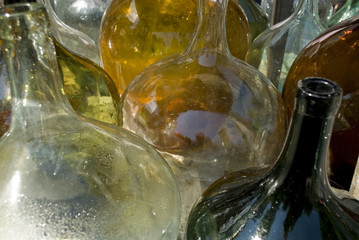 Closeup of a group of old damigiane (demijohns, carboy) glass for wine, of different colors, transparent white, green, brown, in a market in italy