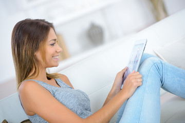 beautiful girl with tablet on sofa