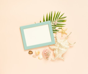 Empty frame and marine items on creme background. Starfish and seashells. Selective focus. Place for text. Flat lay, top view.