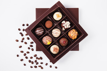 handmade chocolates in a square box and coffee beans near (top view)