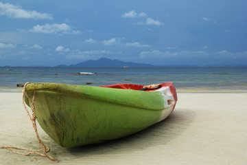 Travel to island Phi Phi, Thailand. The green-red-white boat on the sand beach with sea and a mountain and blue sky on background.