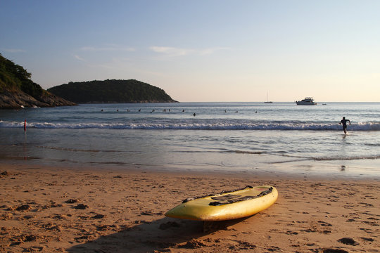 Travel to island Phuket, Thailand. Yellow surfboard on the sand beach with sea, blue sky and a mountain on background.