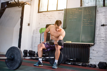 Man is exercising, weight lifting with left arm