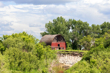 A large old weathered red and gray barn above a stream surrounded by lush green forest of trees under cloudy afternoon sky