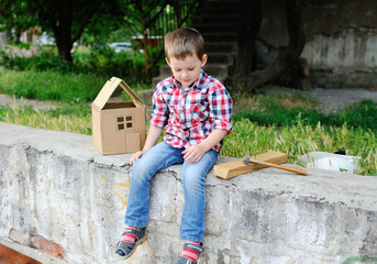 Baby boy playing in a builder and building a cardboard house