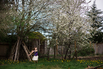 Young girl playing by cherry blossom tree in a garden