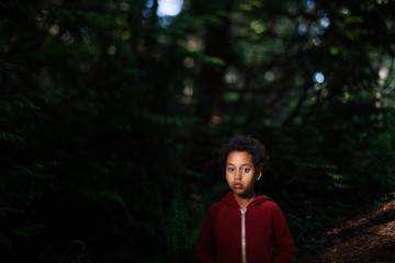 Portrait of child standing in front of tree  in red jumper