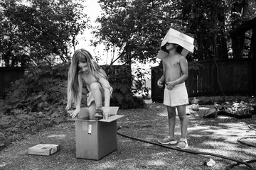 Siblings playing with cardboard boxes in garden, black and white