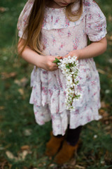 Young girl holding branch of cherry blossom, three quarter length