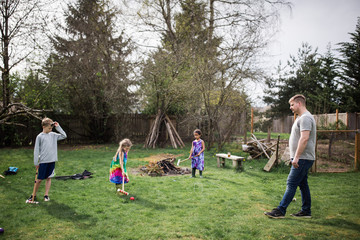 Father and children playing croquet in garden