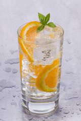 szklanka zimnej wody mineralnej z pomarańczą