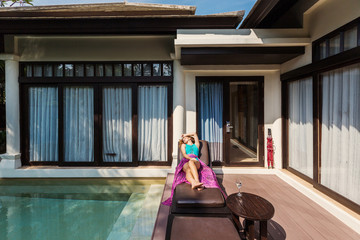 Woman lying on chaise lounge near pool luxury villa, have sunbathe, enjoying summer vacation
